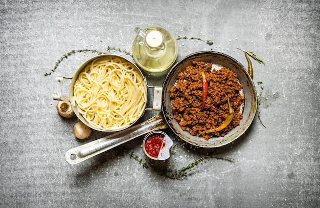 Spaghetti in der pfanne und rinderhackfleisch in einer pfanne mit kräutern und olivenöl. auf dem steintisch. draufsicht