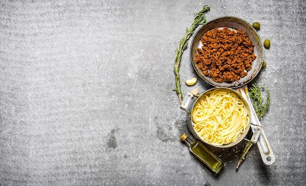 Spaghetti in der pfanne und rinderhackfleisch in einer pfanne mit kräutern und olivenöl. auf dem steintisch. freier platz für text. draufsicht