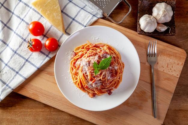 Spaghetti in einem teller auf einem hölzernen hintergrund