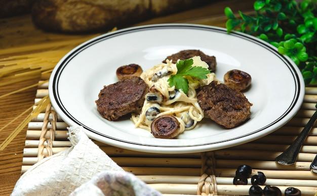 Spaghetti in einer cremigen sauce mit gebratenen champignons und fleischkoteletts