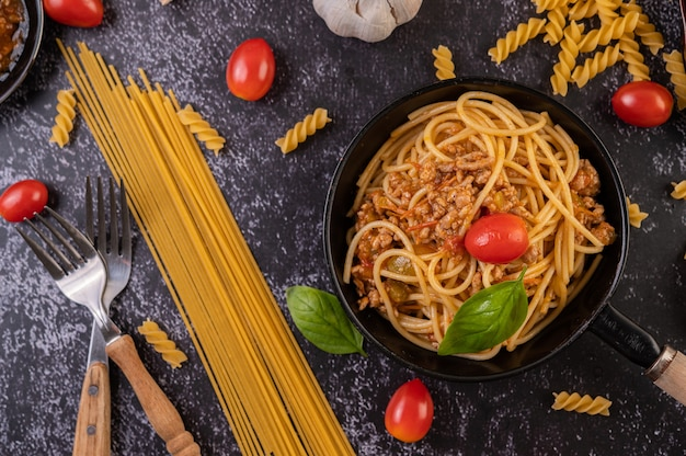 Spaghetti in einer pfanne mit tomaten und basilikum gebraten