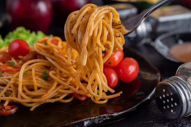 Spaghetti in einer schwarzen tasse mit tomaten und salat.