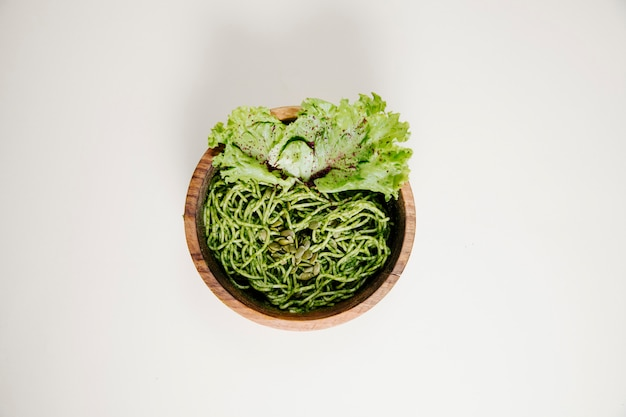Spaghetti in pesto-sauce mit grünem salatblatt.
