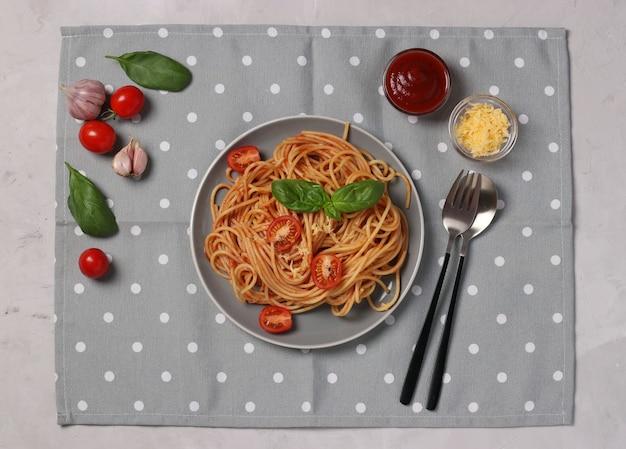 Spaghetti in tomatensauce und kirschtomaten mit basilikum auf teller und grauer serviette.