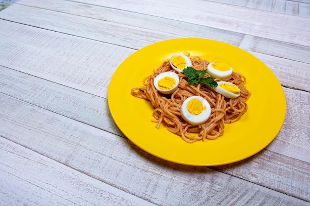 Spaghetti-mahlzeit, tomatensauce, minze auf holztisch. nahaufnahme