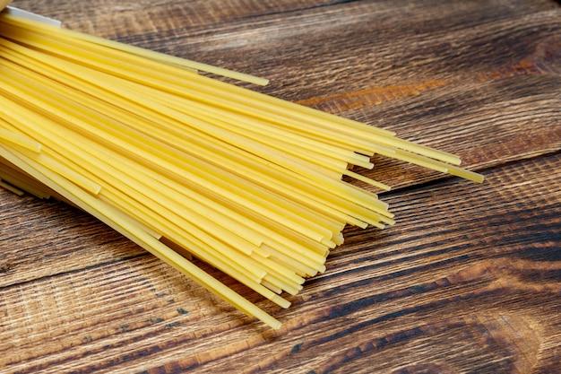 Spaghetti, makkaroni, nudeln, linguine hartweizen italienisch dünn lang auf hölzernem hintergrund schließen selektiven fokus