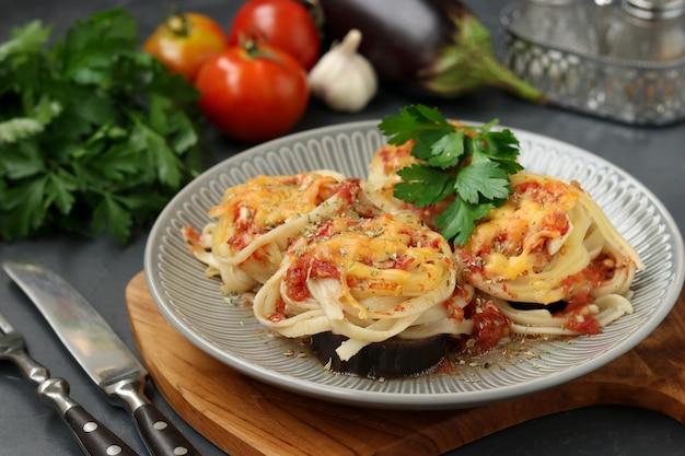 Spaghetti mit auberginen, tomaten, knoblauch und käse auf einem grauen teller auf einem holzbrett. vegetarisches essen