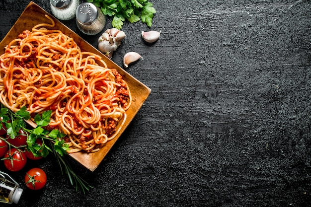 Spaghetti mit bolognese-sauce auf einem teller mit kräutern, tomaten und knoblauch. auf rustikalem hintergrund