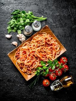 Spaghetti mit bolognese-sauce auf einem teller mit kräutern, tomaten und knoblauch. auf rustikaler oberfläche
