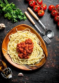 Spaghetti mit bolognese-sauce in einem teller mit tomaten, petersilie und knoblauch. auf rustikalem hintergrund