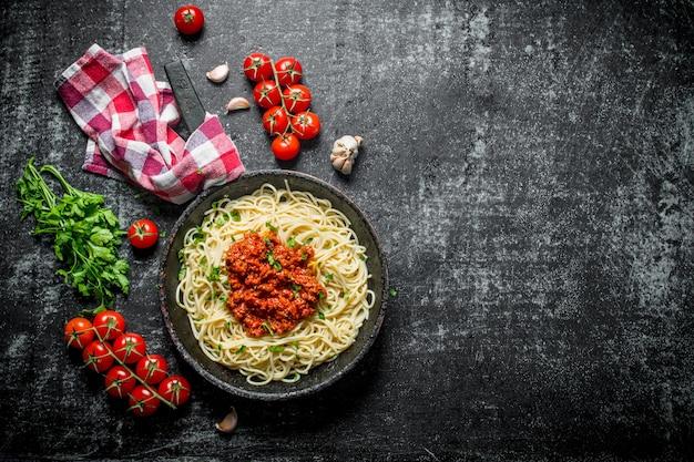 Spaghetti mit bolognese-sauce in einer pfanne mit serviette und tomaten. auf rustikalem hintergrund