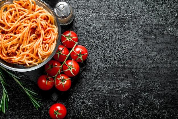 Spaghetti mit bolognese-sauce in einer schüssel mit tomaten, rosmarin und gewürzen. auf schwarzem rustikalem hintergrund