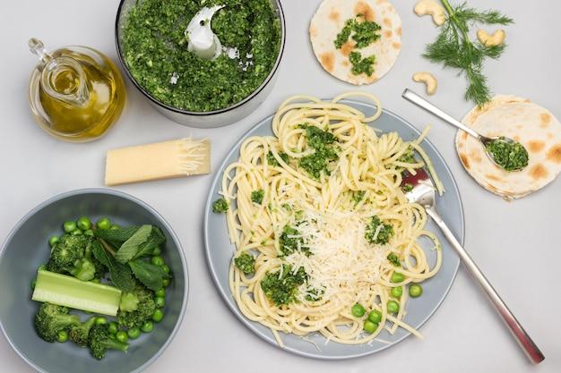 Spaghetti mit brokkolipaste und gabel auf keramikplatte