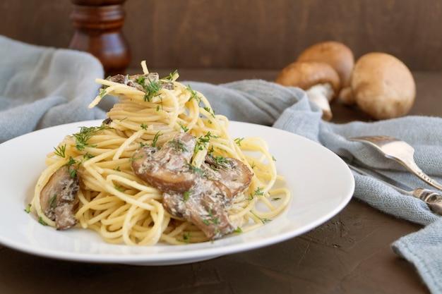 Spaghetti mit champignons in sahnesoße. auf dunklem hintergrund