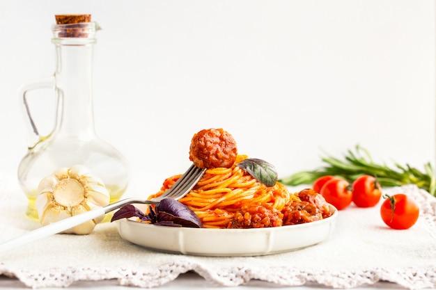 Spaghetti mit fleischbällchen, tomatensauce und basilikum. fleischbällchen mit spaghetti und basilikum auf einer gabel. italienische pasta. new yorker fleischbällchen, tomatensauce, alle bio-lebensmittel aus dem garten. leckeres herzhaftes mittagessen.