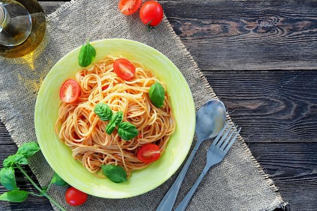 Spaghetti mit frischen tomaten und basilikum in einem grünen teller auf einem rustikalen holztisch