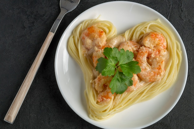 Spaghetti mit garnelen in sahnesauce. in form eines herzens