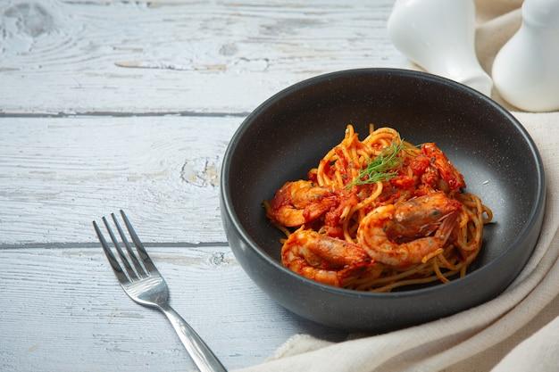 Spaghetti mit garnelen in tomatensauce auf weißem holzhintergrund