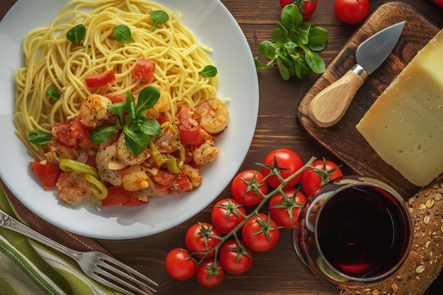 Spaghetti mit garnelen, kirschtomaten und gewürzen auf holz.