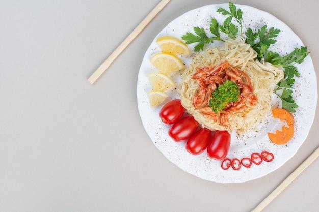 Spaghetti mit gehacktem huhn und gemüse auf weißem teller