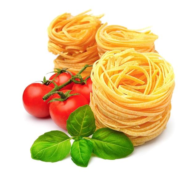 Spaghetti mit gemüse und basilikum auf weiß