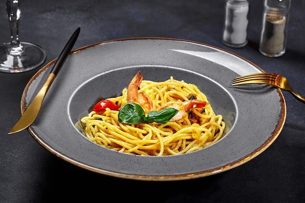 Spaghetti mit getrockneten tomaten, garnelen und basilikum