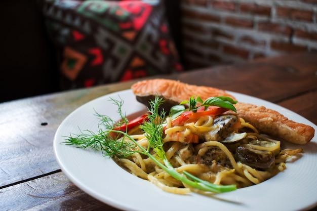 Spaghetti mit grünem curry und ein großes stück lachs.