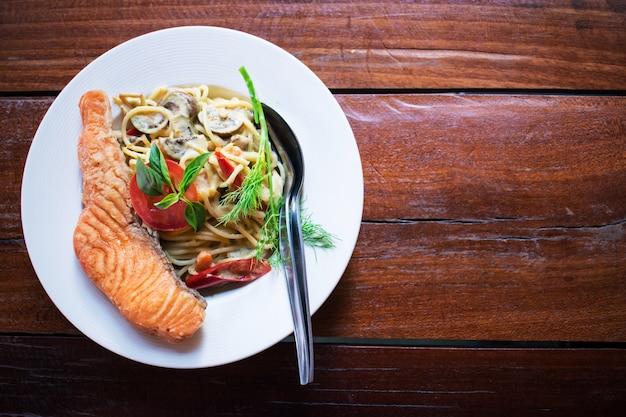Spaghetti mit grünem curry und einem großen lachs