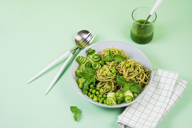 Spaghetti mit grüner pesto-sauce, garniert mit frischer gurke und grünen erbsen, kopie des raumes