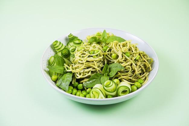 Spaghetti mit grüner pesto-sauce, garniert mit frischer gurke und grünen erbsen