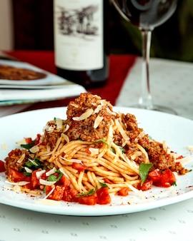 Spaghetti mit hackfleisch, tomatenwürfeln, käse und minze