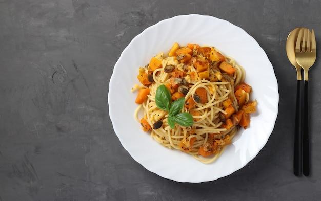 Spaghetti mit kürbis und kürbiskernen in einem weißen teller auf dunkelgrauem hintergrund. sicht von oben. platz für text