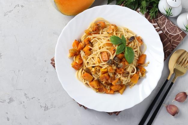 Spaghetti mit kürbis und kürbiskernen in einem weißen teller auf einem grau.