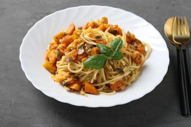 Spaghetti mit kürbis und kürbiskernen in einem weißen teller auf einer dunkelgrauen oberfläche. nahansicht