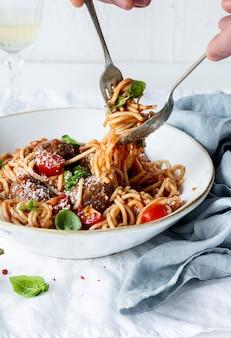 Spaghetti mit marinara-tomatensauce, garniert mit parmesan und basilikum food-fotografie