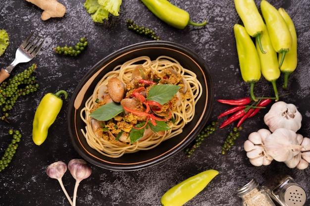 Spaghetti mit muscheln in einem schwarzen teller mit chilis frischer knoblauch und pfeffer.