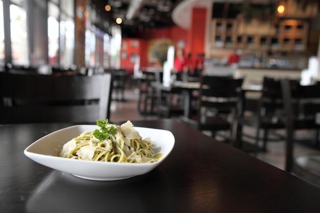 Spaghetti mit pesto-sauce auf holztisch