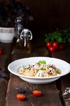 Spaghetti mit pilzen und schinken in sahnesauce auf einem holztisch