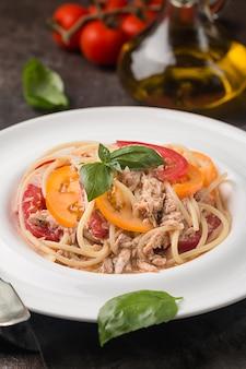 Spaghetti mit thunfisch-tomaten und knoblauchsauce auf weißem teller über dunklem hintergrund
