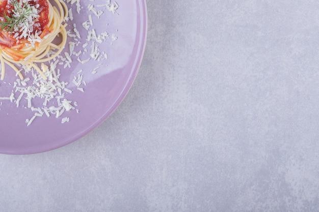 Spaghetti mit tomatennudeln auf lila teller.