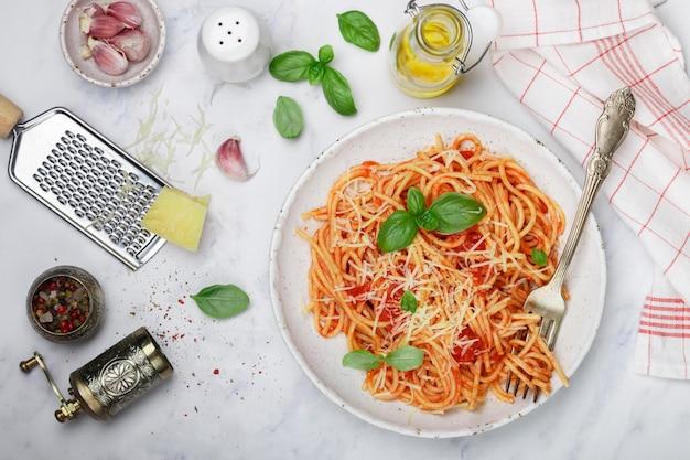 Spaghetti mit tomatensauce mit knoblauch, basilikum, gewürzen, olivenöl und parmesan
