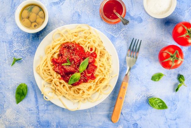 Spaghetti mit tomatensauce, oliven und basilikum