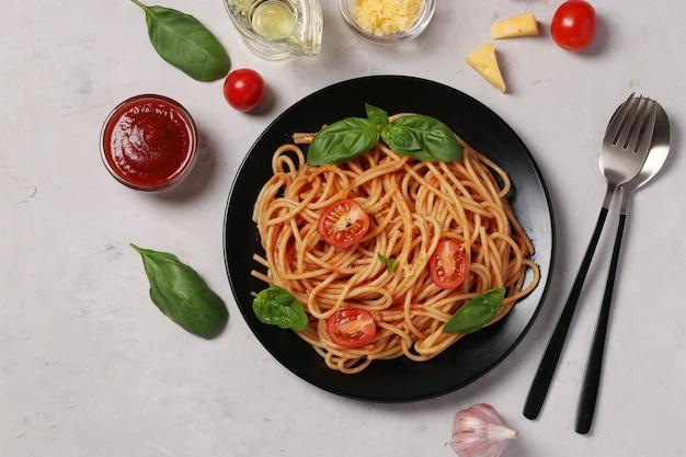 Spaghetti mit tomatensauce und kirschtomaten mit basilikum auf schwarzem teller auf licht