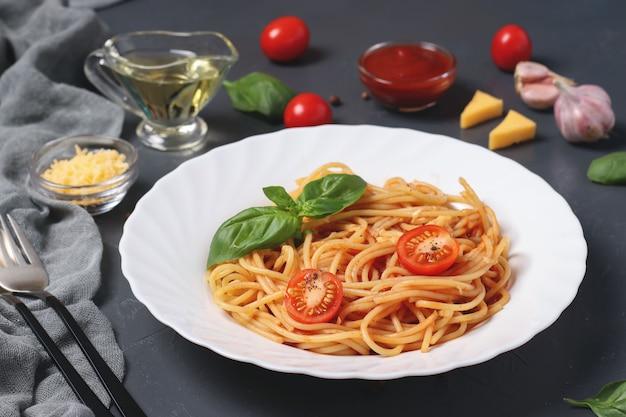 Spaghetti mit tomatensauce und kirschtomaten mit basilikum