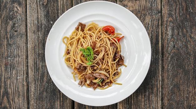 Spaghetti mit weißem teller auf dem tisch