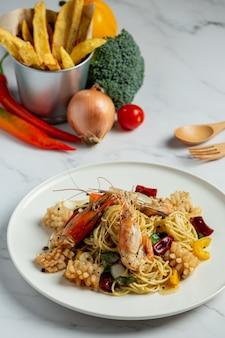 Spaghetti mit würzigen gemischten meeresfrüchten auf marmorhintergrund