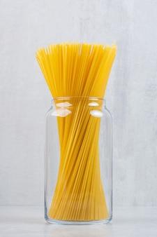Spaghetti-nudeln in einem glas auf dem marmor.