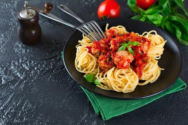Spaghetti-nudeln mit fleischbällchen, tomatensauce und basilikum auf dunklem hintergrund.
