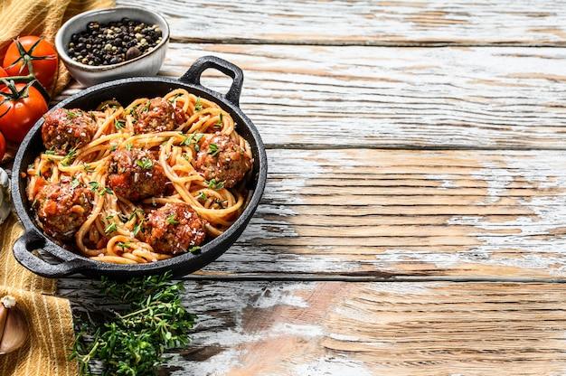 Spaghetti-nudeln mit fleischbällchen und tomatensauce. weißer hölzerner hintergrund. draufsicht. speicherplatz kopieren
