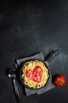 Spaghetti-nudeln mit herzförmiger tomatensauce